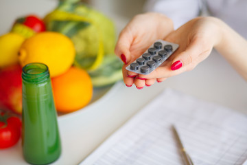 Female Nutritionist Holding Blisters of Pills