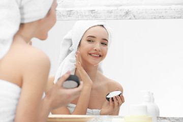 Teenage girl with acne problem using cream while looking in mirror indoors