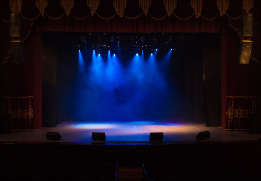 An empty stage of the theater, lit by spotlights and smoke before the performance