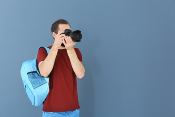 Young photographer with professional camera on color background