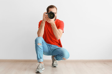 Young photographer with professional camera near white wall