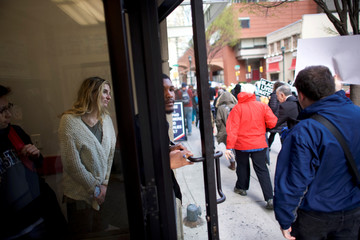 A woman watches interfaith clergy leaders march from the Center City Starbucks, where two black men were arrested, to other nearby stores in Philadelphia, Pennsylvania