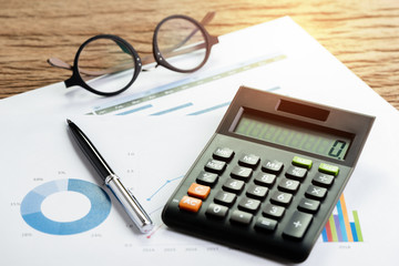 Company performance or financial review and calculations concept with pen and calculator and eyeglasses on graph and pile chart paper on wooden table, KPI or client campaign analysis