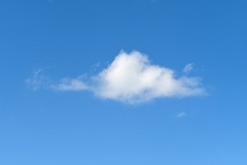 single fluffy white cloud in bright blue sky