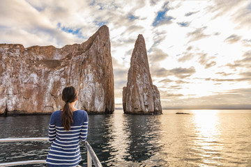 Galapagos Cruise ship tourist on boat looking at Kicker Rock nature landscape. Iconic landmark and tourist destination for birdwatching, diving and snorkeling, San Cristobal Island, Galapagos Islands.