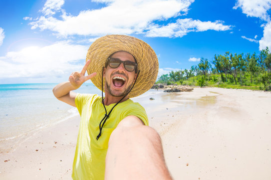 Handsome man having fun taking a selfie at the beach on holiday