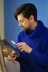 Artist in blue sweater draws mixes of oil paints with palette knife. He holds palette and brush bristle.