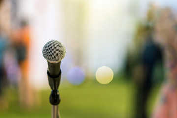 Microphone on the stage over the Abstract blurred photo of green grass with bokeh of light background, Musical and presentation concept