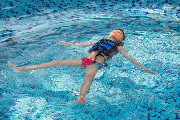 Boy in vest at pool swiming on back. Childhood, leisure, healthy lifestyle theme
