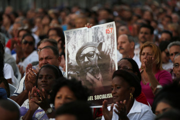 A woman holds a picture of late Cuban President Fidel Castro during a ceremony to mark the 57th anniversary of the declaration of the socialist character of the Cuban Revolution in Havana