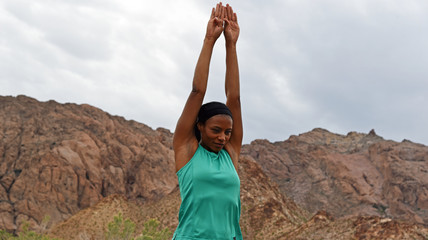 Woman doing stretching or yoga exercises in the mountains
