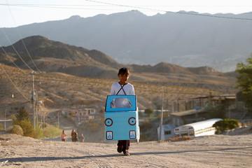 Jazmin, 9, carries a cardboard car to be used in a play in her school at Anapra neighborhood in Ciudad Juarez