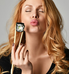 Woman with sushi hold philadelphia rolls in hands with chopsticks kissing on a light gray background