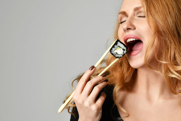 Woman with sushi hold philadelphia rolls in hands with chopsticks on a light gray