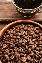 cup of coffee and coffee beans in wooden bowl
