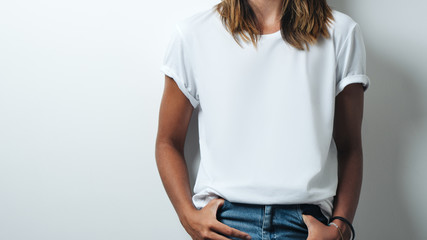 Pretty woman in white blank t-shirt, empty wall, studio close-up Wall mural