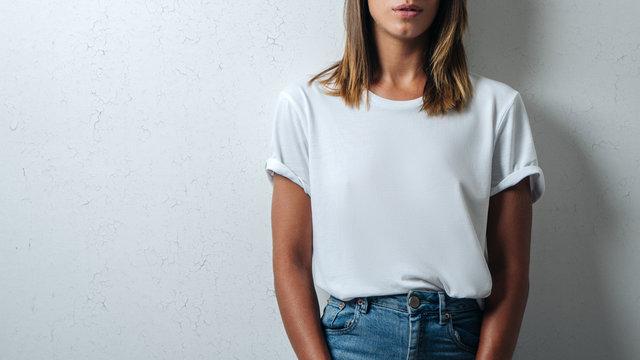 Pretty woman in white blank t-shirt, grunge wall, studio close-up