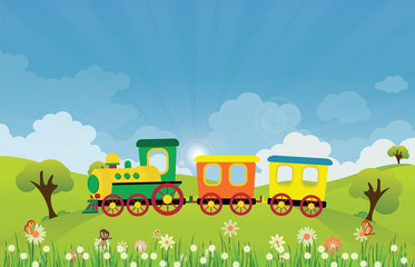 Toy train riding on Spring summer meadow landscape with sun rays and flowers.