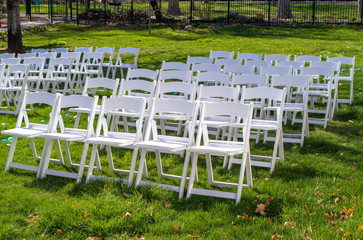 Rows of empty white chairs on some green grass set up for a wedding.