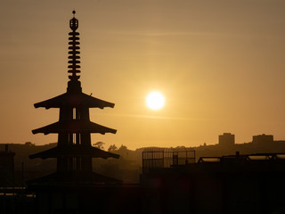 Silhouette of Peace Pagoda in San Francisco, CA while sun is setting to right