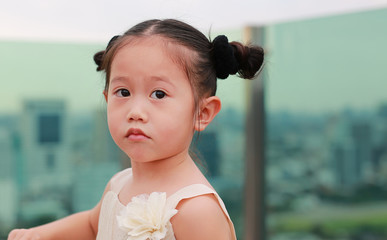 Portrait of child girl at the rooftop of building.
