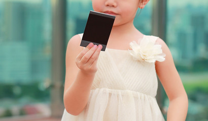 Close-up little child girl in cream dress hold and looking photo in her hands at the rooftop of building.