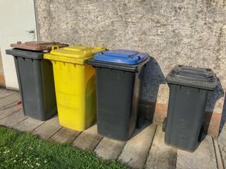 Verschiedene Mülltonnen an einer Hauswand