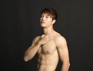 muscular young man isolated on black background