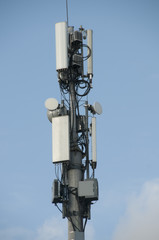 Cell tower closeup against a white sky.