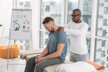Muscle relaxation. Smart nice man standing behind his patient while doing a shoulder massage