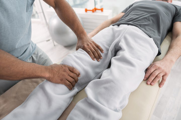 Professional treatment. Top view of male hands doing a medical massage for the patient