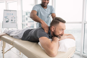 Therapeutic massage. Joyful nice bearded man smiling while enjoying the therapeutic massage