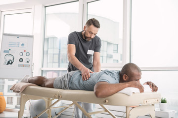Skillful orthopedist. Skilled bearded man doing a back massage for his patient while working as an orthopedist