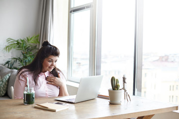 Pretty girl with curvy body and dark hair smiling excitedly, holding hand on her chest and looking at laptop screen, reading astonishing news online, surfing internet, sitting at window. Copy space