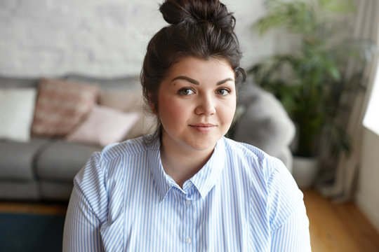 Beauty and body positivity concept. Picture of happy attractive young brunette plus size woman with hair bun and beautiful features posing indoors against gray couch and plant pot background