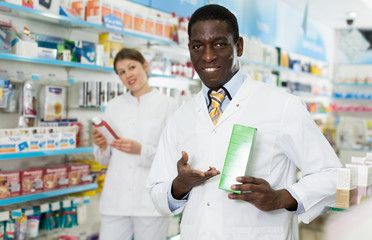Positive woman and man pharmacists offering medicines