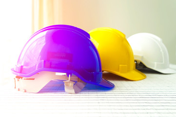 The blue, yellow and white safety helmet stacking on table with the blueprint and measuring tools at construction site for Engineer.
