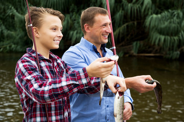 Man with teenager boy showing catch fish
