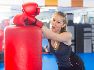 Portrait of young female with  punching bag