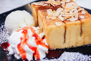 Honey Toast. Bread buttered toast. Topped with honey, banana and fruit decorations. A side of whipped cream, ice cream.
