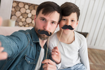 Father is the biggest example of success and courage! Serious young man making a selfie with his son and holding moustache masks.