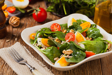 Delicious salad of fresh spinach, boiled egg, tomatoes, nuts and sunflower seeds