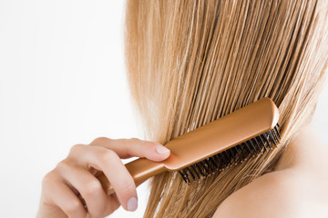 Young woman with comb brushing her wet, blonde, perfect hair after shower on the white background. Care about beautiful, healthy and clean hair. Beauty salon concept. Side view.