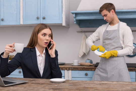 Terrible news. Shocked determined woman discussing work on the phone and her husband washing the dishes