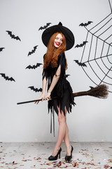 Halloween Concept - Happy elegant witch enjoy playing with broomstick halloween party over grey background.