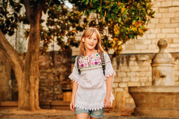 Adorable little girl tourist with backpack on the streets of Provence at sunset, travel with kids