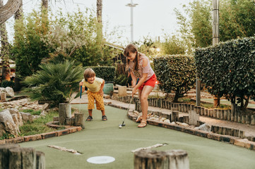Group of two funny kids playing mini golf, children enjoying summer vacation