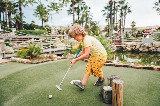 Funny kid boy playing mini golf, child enjoying summer vacation