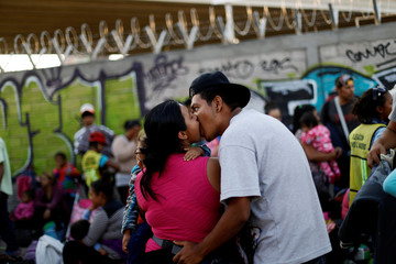 A couple of Central American migrants, moving in a caravan through Mexico, kiss next to the railway as they wait to try and board a freight train, in Irapuato