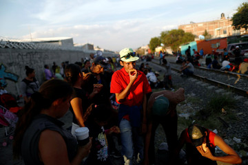 A Central American migrant, moving in a caravan through Mexico, eats as he waits next to the railway to try and board a freight train, in Irapuato